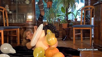Mature model Doris Dawn plays with balloons and her hairy pussy